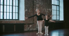Adult ballerina teaching a little girl to dance class loft design Stock Footage