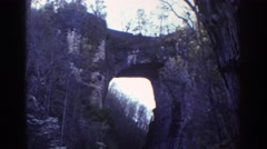 1971: a man walks down a road towards a large hole in a wall front RICHMOND Stock Footage