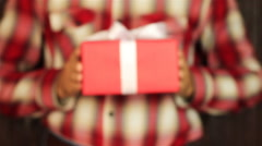 Young man gives a gift on wooden background. Red gift box with white ribbon Stock Footage