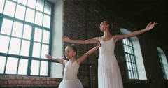 Adult ballerina teaching a little girl to dance class loft design Stock Footage