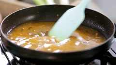 Sauteeing : cooking curry paste in a pan on the stove Stock Footage