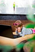 Little girl using laptop. Child in pink skirt and pink boots, pink sunglasses Stock Photos