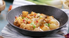 Sprinkle green onion on spicy chicken feet and fish cakes stew in a bowl Stock Footage