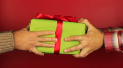 Young man gives a gift on red background. Green gift box with red ribbon opening Stock Footage
