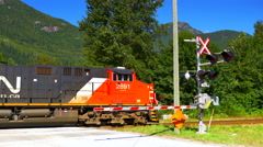 4K Crossing Barrier and Train Passing Behind, Large Red Diesel Locomotive Engine Stock Footage