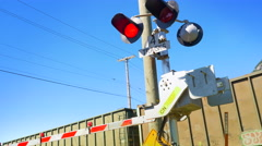 4K Train Car Passes Behind Flashing Road Crossing Barrier, Red Lights, Blue Sky Stock Footage