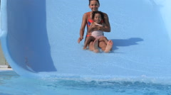 Little girl of mixed race and his mother falling down from the water slide Stock Footage