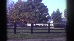 1976: farm with a house in the back, field surrounded by a brown wooden fence Stock Footage