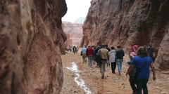 Tourists walking along the canyon in Petra Stock Footage