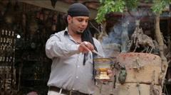 Bedouin kindles coals for hookah outside a souvenir shop Stock Footage