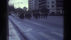 1976: military band leads traditionally-dressed marchers in parade on city Stock Footage