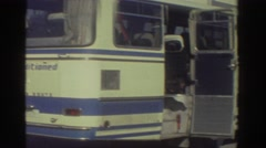 1976: several people are in the vicinity of a parked passenger bus  Stock Footage
