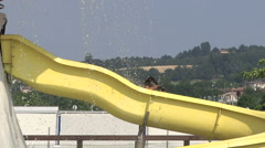 Little girl of mixed race and her mother coming down on the flume in aquapark Stock Footage