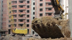 Excavator digging a hole at a construction site Stock Footage
