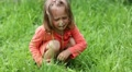 Little girl sits on green grass and crying HD Footage