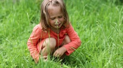 Little girl sits on green grass and crying Stock Footage