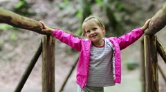 Little girl stands on a wooden bridge and smiles Stock Footage