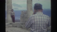 1976: man taking picture of toursit at ancient stone temple ruin GREECE Stock Footage
