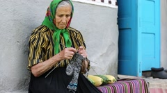 Old woman sits on bench and knits woollen socks Stock Footage