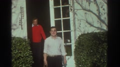 1976: waving man in white shirt and jolly man in red sweater leave from door  Stock Footage