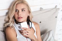 Dreamy woman holding smartphone Stock Photos