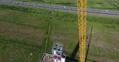 Crane lift chimney pipe segment. Аerial, workers on the top Stock Footage