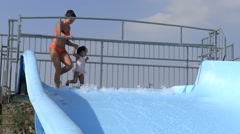 Little girl of mixed race sits on her mother and goes with her down the slide Stock Footage