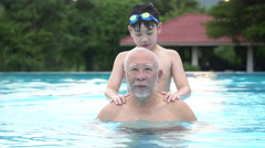 Asian grandchildren and grand parents swimming in pool. Stock Footage