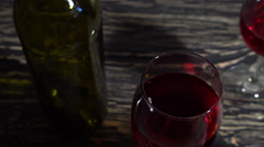 Bottle and glass of red wine on a wooden table Stock Footage