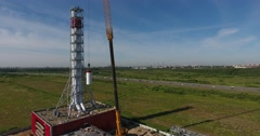 Chimney pipe construction aerial, the crane lifts the pipe segment flying around Stock Footage