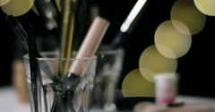 Make up objects and hand putting back pen in a glass. Stock Footage