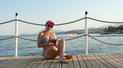 Pretty woman sitting on the pier with smartphone, slow motion 1 Stock Footage