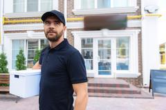 Bearded postman standing outdoors Stock Photos