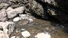 Water Flows Between Rocks and Water Drops Falling from Cliff Slow Motion Stock Footage