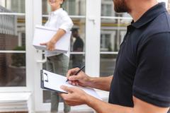 Selective focus on postman checking his clipboard Stock Photos