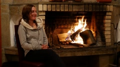 Auburn beauty young woman warming up at fire place in winter Stock Footage