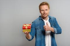 Young male holding a present and giving thumb Stock Photos