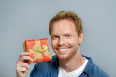 Smiling man holding his gift Stock Photos