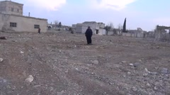 Syria, February 22, 2016: Old woman walk on the ground, ISIS war Stock Footage