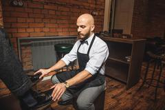 Bald bearded man preparing to shoe shine Stock Photos