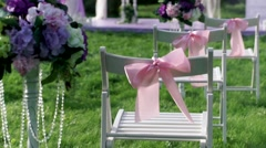 White chairs with pink bows close up outdoors at wedding verinke. Wedding Stock Footage