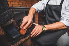 Craftsman shoe shining footwear in front of him Stock Photos