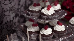 Chocolate cupcakes with whipped cream and raspberry lie on a candy bar Stock Footage
