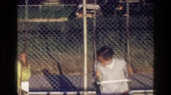 1976: children playing happily on a swing set at an elementary schools HARLEM Stock Footage