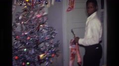 1976: a man busy decorating the house for christmas, looking for a proper place Stock Footage