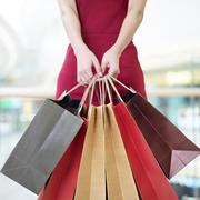 Young woman carrying paper shopping bags in modern mall Stock Photos