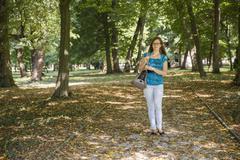 Woman walk in green park carrying a cat transport bag Stock Photos