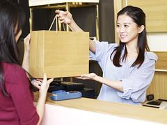 Salesclerk handing merchandise to customer Stock Photos