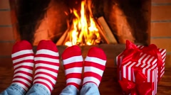 Couple in Christmas socks near fireplace Stock Footage