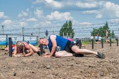 Athletes creep under barbed wire. Tyumen. Russia Stock Photos